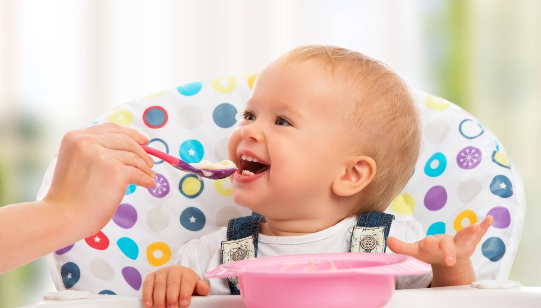 Jak walczyć z rotawirusem u dzieci? Jak pokonać grypę żołądkową? Mama karmi kaszką niemowlę, siedzące przy stole w specjalnym krzesełku dla dzieci.