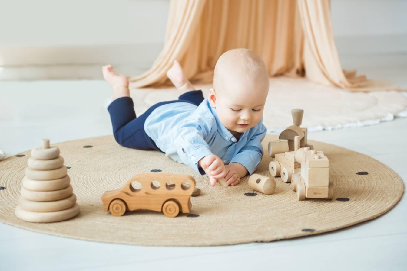 Ekorodzicielstwo - jakie ekologiczne zabawki dla dzieci wybrać? Niemowlę bawi się drewnianymi zabawkami w swoim pokoju dziecięcym.
