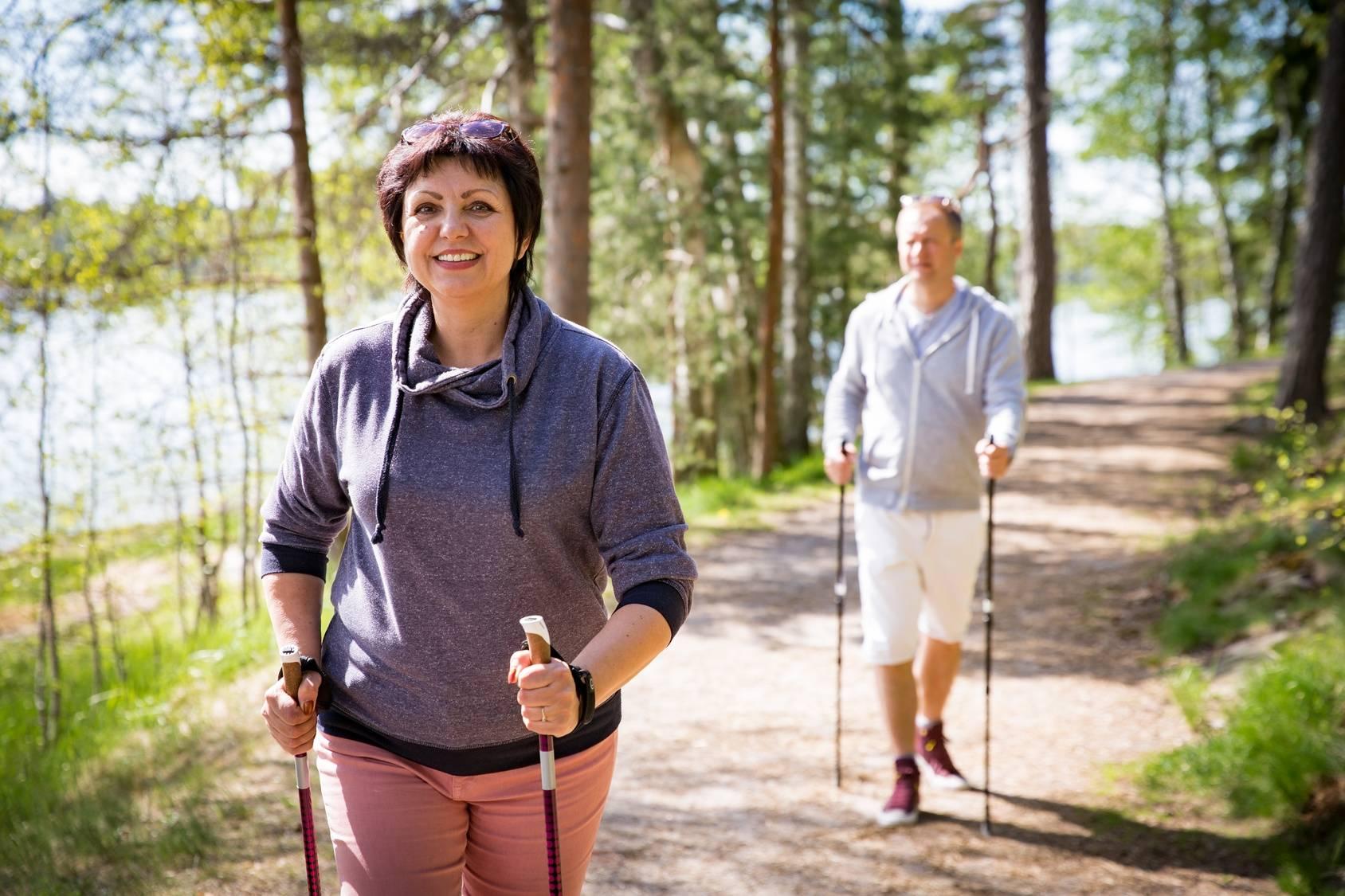 Nordic walking dla początkujących - gdzie i jak uprawiać ten sport? Mężczyzna i kobieta uprawiają nordic walking w lesie nad wodą.