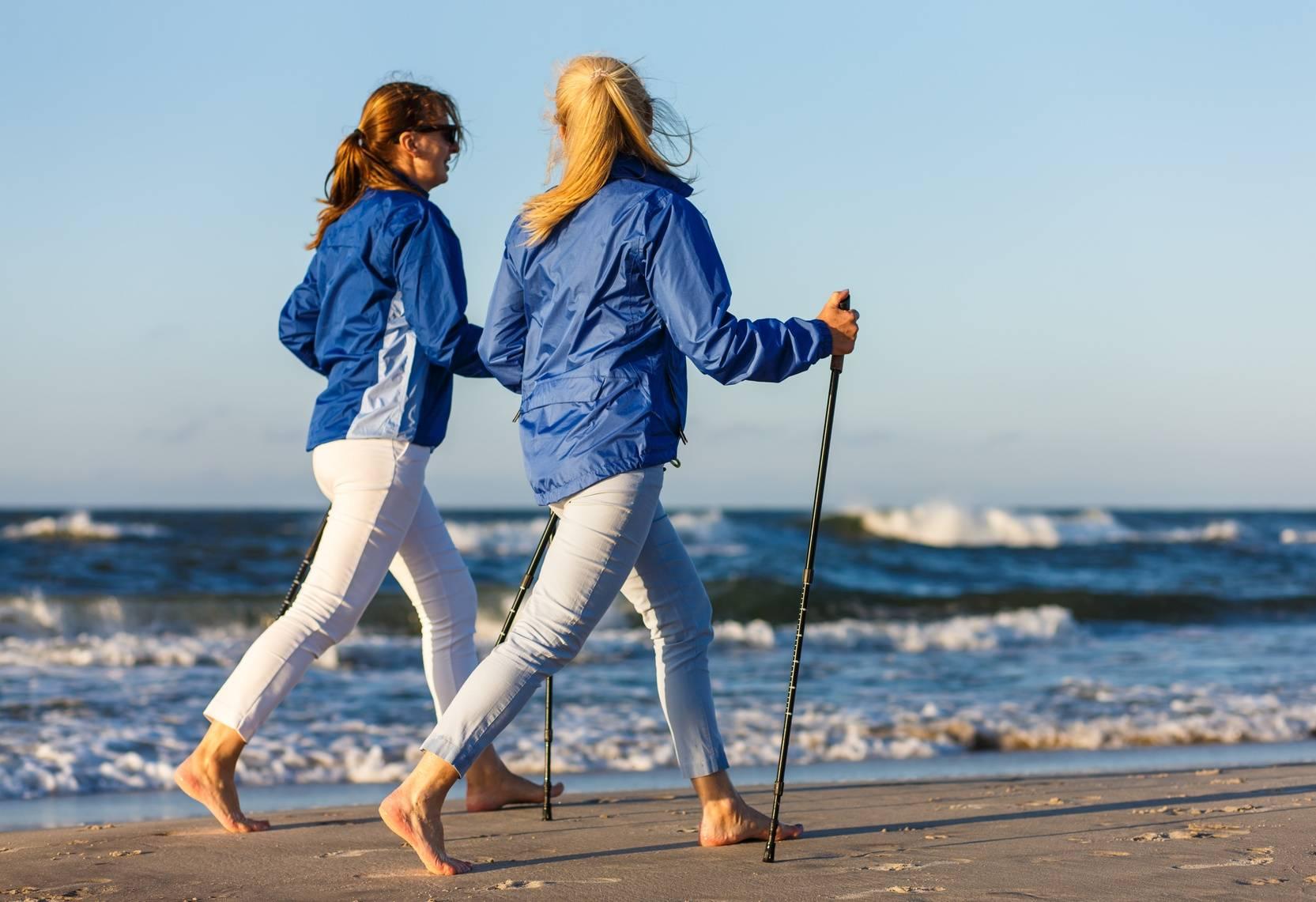 Dwie kobiety uprawiają nordic walking na plaży - jak uprawiać nordic walking. dla początkujących.