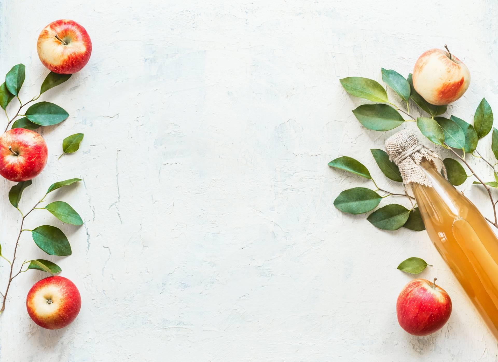 Ocet jabłkowy na włosy. Na jasnym blacie po bokach kadru leżą jabłka, listki jabłoni i butelka z octem jabłkowym.