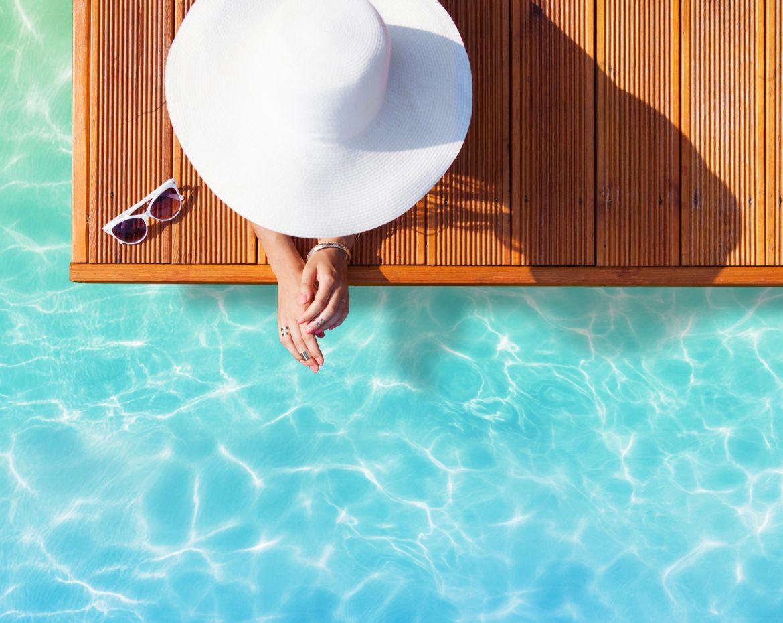 Jak się bezpiecznie opalać przy problemach z cerą? Kobieta wypoczywa w basenie, chroniąc się przed słońcem wielkim kapeluszem.
