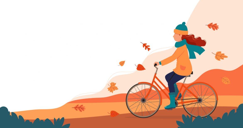 10 produktów wzmacniających odporność i zwalczających wirusy. Ilustracja w jesiennych barwach: kobieta jedzie na rowerze w swetrze, czapce i szaliku jesienią.