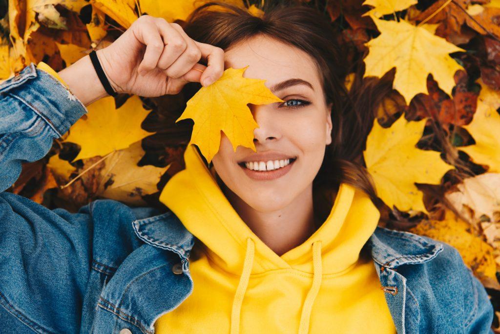 Odporność - czym jest, jak działa i jak ją budować? Dziewczyna w żółtej bluzie i kurtce jeansowej leży w jesiennych liściach i trzyma żółty liść przy twarzy, zasłaniając nim oko.