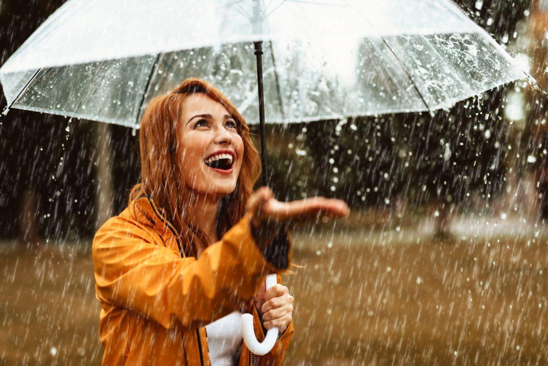 Czynniki obniżające odporność. Co wpływa na obniżoną odporność? Kobieta w żółtym płaszczyku pod przezroczystym parasolem wystawia rękę na deszcz.