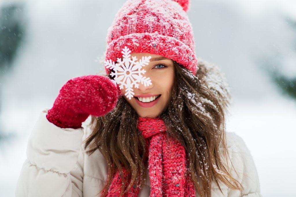 Jak wzmocnić odporność w 7 krokach? Kobieta w kurtce puchowej, czerwonej czapce i szaliku w zimowej scenerii uśmiecha się do aparatu, przykładając do oka ozdobny płatek śniegu.