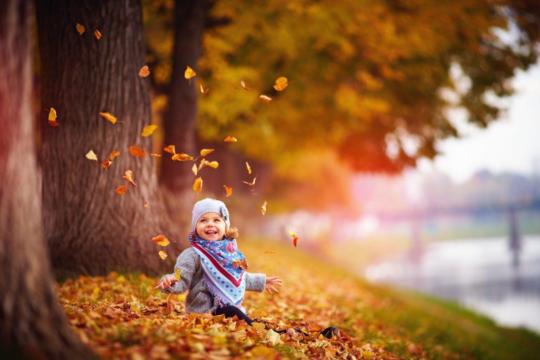 Jak wzmocnić odporność u dzieci? Mała dziewczynka bawi się jesiennymi liśćmi.