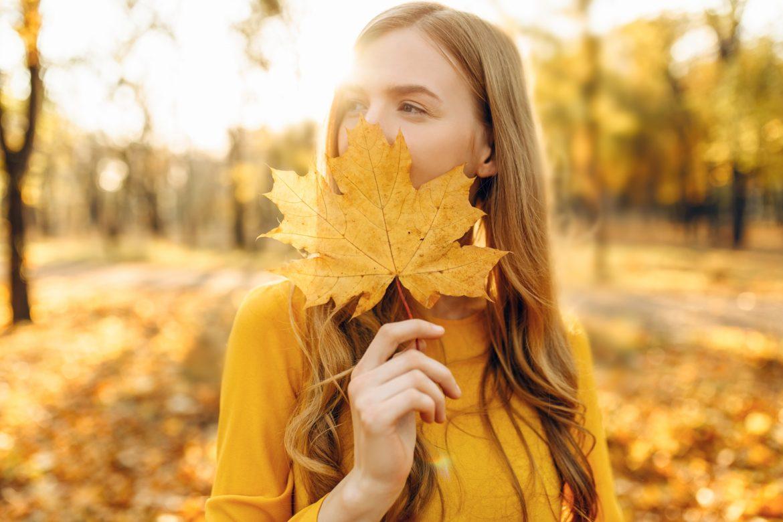 Naturalne sposoby na wzmocnienie odporności. Jak wzmocnić odporność jesienią i zimą? Młoda dziewczyna stoi w lesie i przykłada jesienny żółty liść do twarzy.