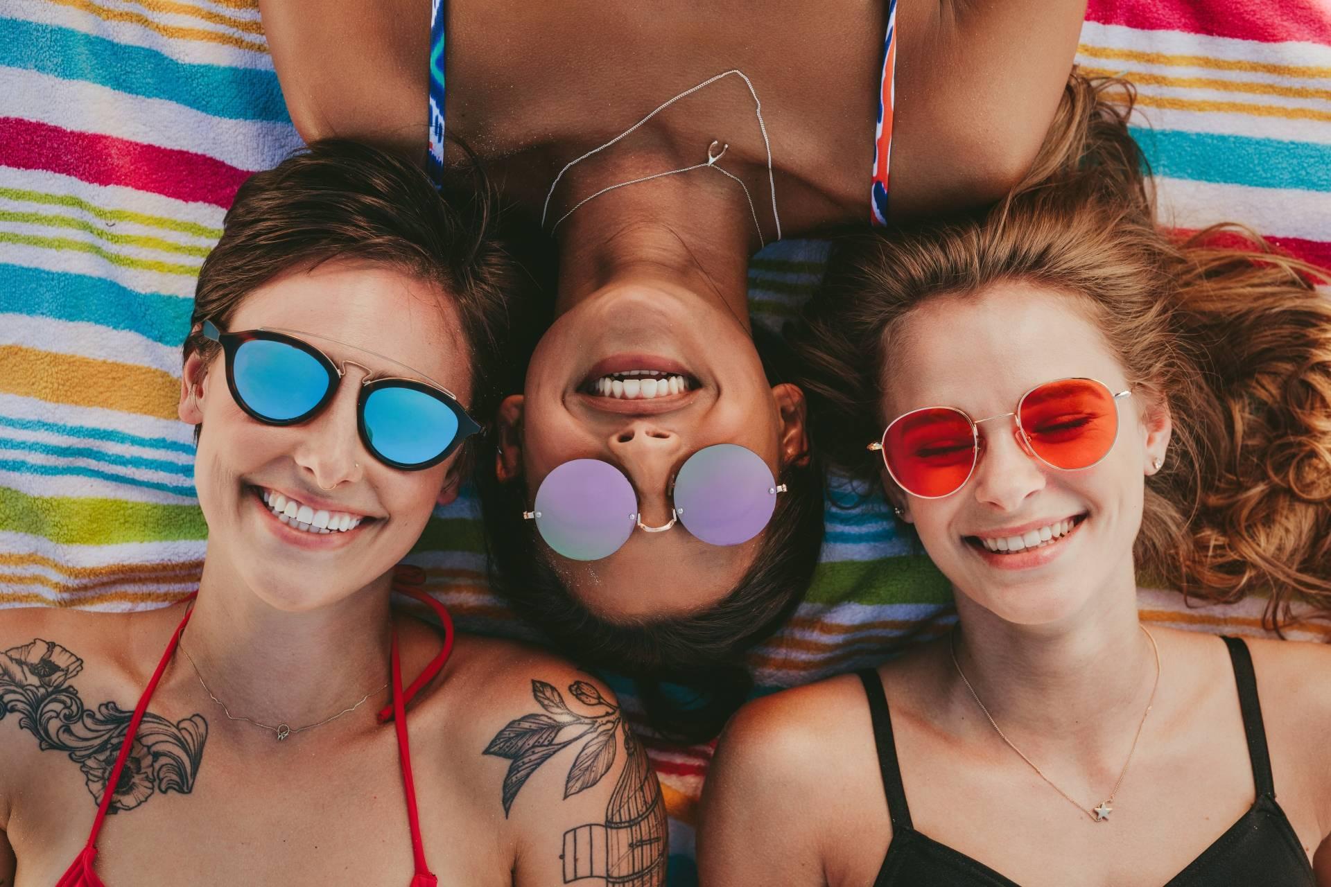 Jak się bezpiecznie opalać przy problemach z cerą? Trzy przyjaciółki w okularach przeciwsłonecznych opalają się na plaży.