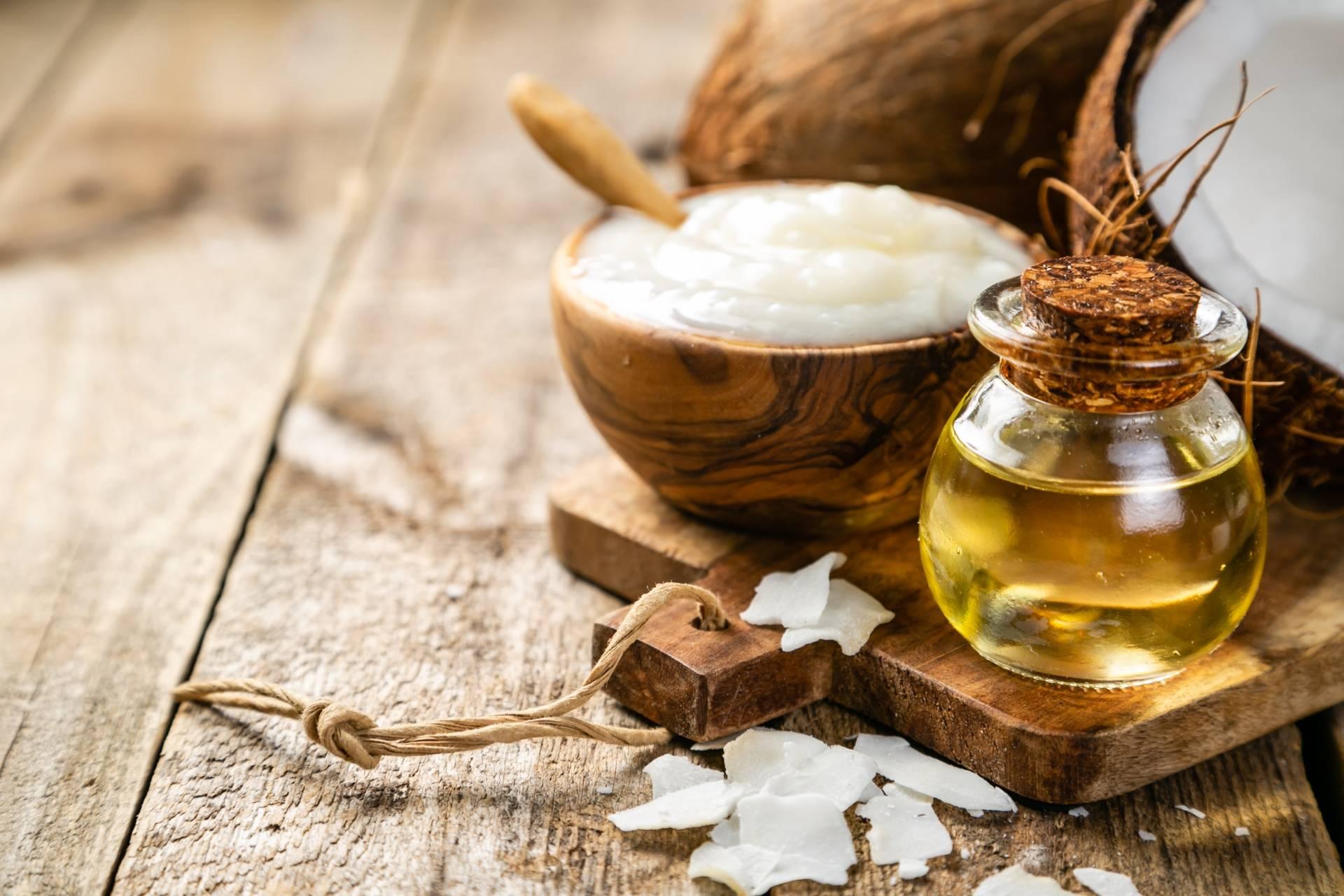 Olej kokosowy w miseczce i olej w butelce na drewnianym blacie.
