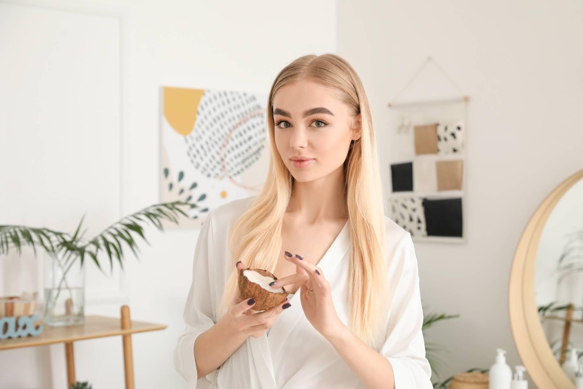 Olej kokosowy na włosy. Młoda atrakcyjna dziewczyna stoi w łazience i trzyma w ręku połówkę kokosa.