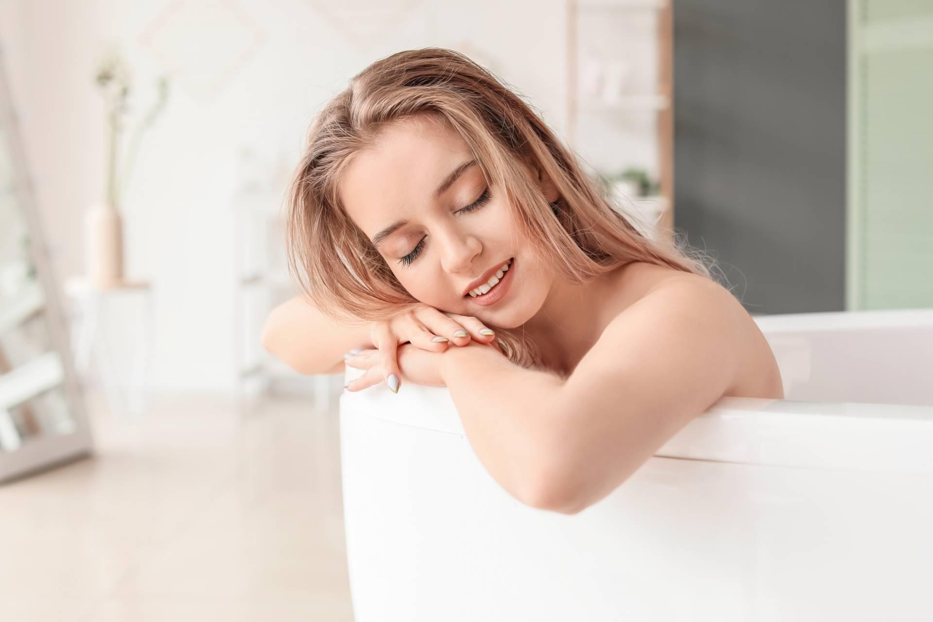 Młoda zrelaksowana kobieta bierze kąpiel w wannie. Olejek arganowy dodany do kąpieli.