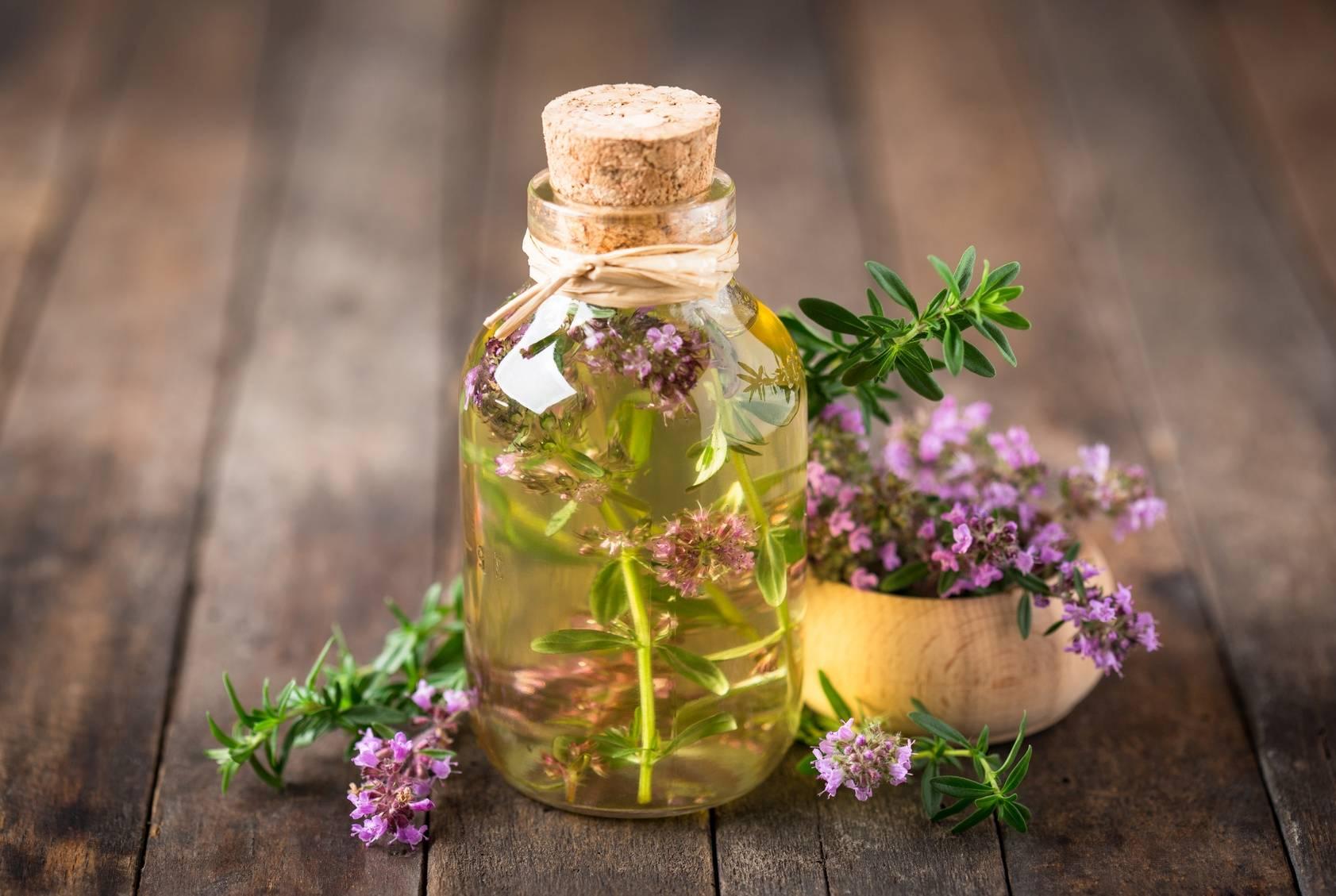 Ziołowe leki na przeziębienie z tymiankiem. Mała buteleczka oleju z tymiankiem w środku stoi na drewnianym blacie. Obok leży miseczka z kwiatem tymianku.