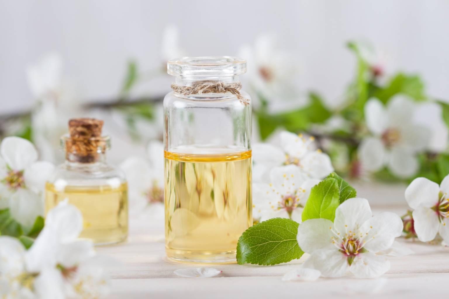 Czym są olejki eteryczne i jak działają? Na czym polega aromaterapia? Jasnożółty olejek w przezroczystej buteleczce stoi na jasnym blacie w otoczeniu białych kwiatów jabłoni.