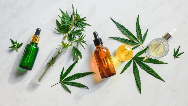 Na jakie problemy zdrowotne pomaga olejek CBD? Widok z góry na rozłożone na płasko buteleczki z olejkiem CBD oraz liście konopi leczniczej.
