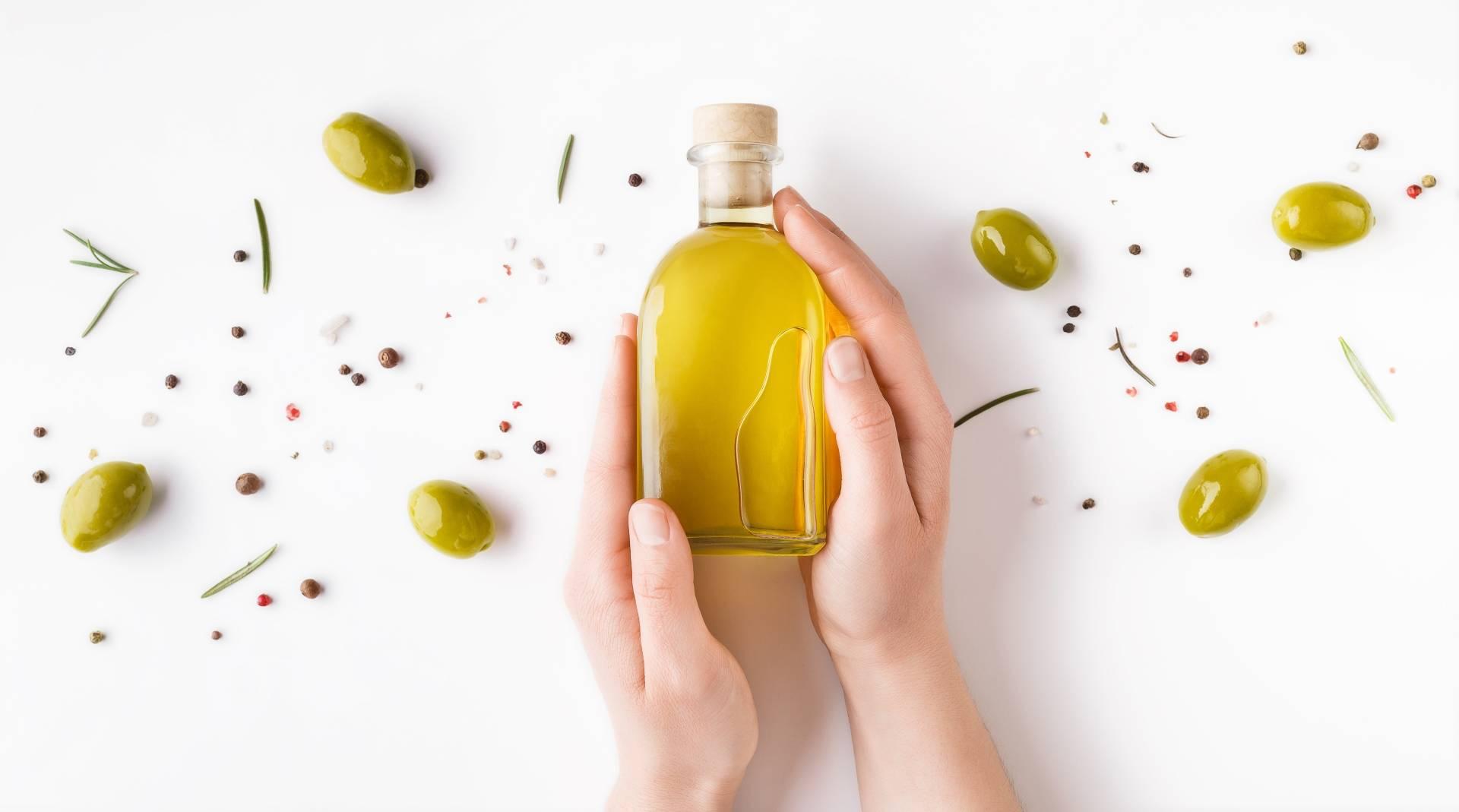 Zdrowe tłuszcze w diecie przeciwgrzybiczej. Kobiece dłonie trzymają butelkę oliwy z oliwek na białym tle. Obok leżą oliwki i suszone zioła.