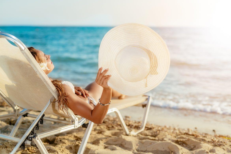 Plamy na skórze - jak uniknąć przebarwień słonecznych? Młoda kobieta z kapeluszem w ręku opala się na plaży na leżaku.