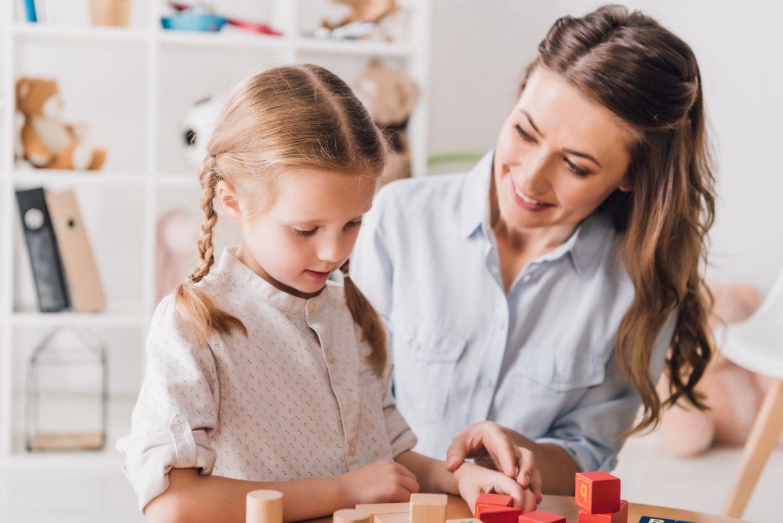 Wysoko wrażliwe dziecko - jak się nim dobrze zaopiekować? Młoda mama pomaga córeczce ułożyć klocki.
