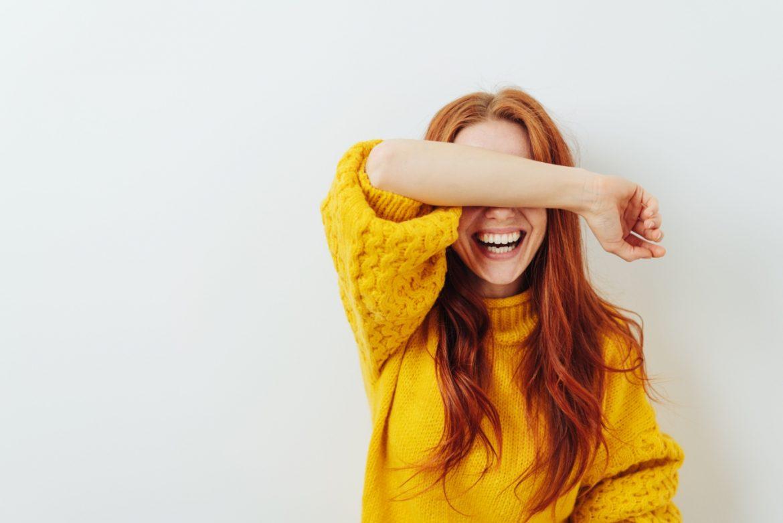 Osteoporoza - objawy, przyczyny, leczenie. Jak wygląda dieta przy osteoporoza i jak ćwiczyć. Rudowłosa dziewczyna w żółtym swetrze śmieje się zakrywając oczy przedramieniem.