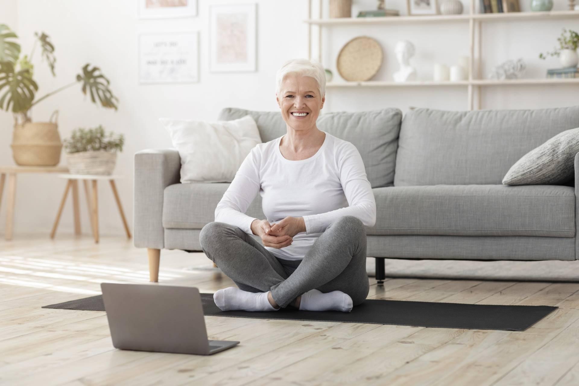 Osteoporoza - co warto o niej wiedzieć? Jak leczyć osteoporozę i jak ją diagnozować? Kobieta seniorka ćwiczy w domu na macie.