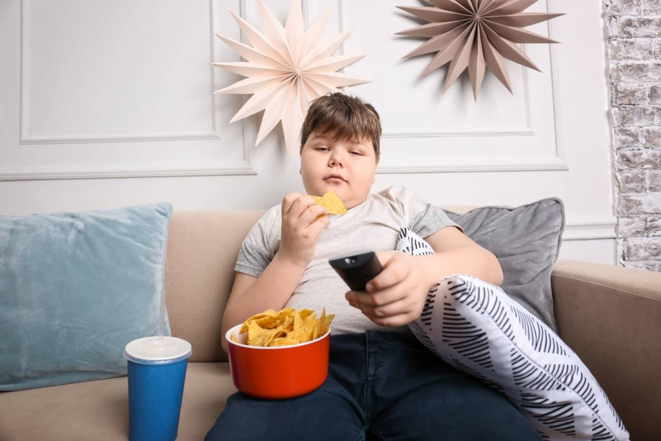 Otyłość u dzieci - jak z nią walczyć? Chłopiec z dużą nadwagą siedzi na kanapie, je chipsy i ogląda telewizję.