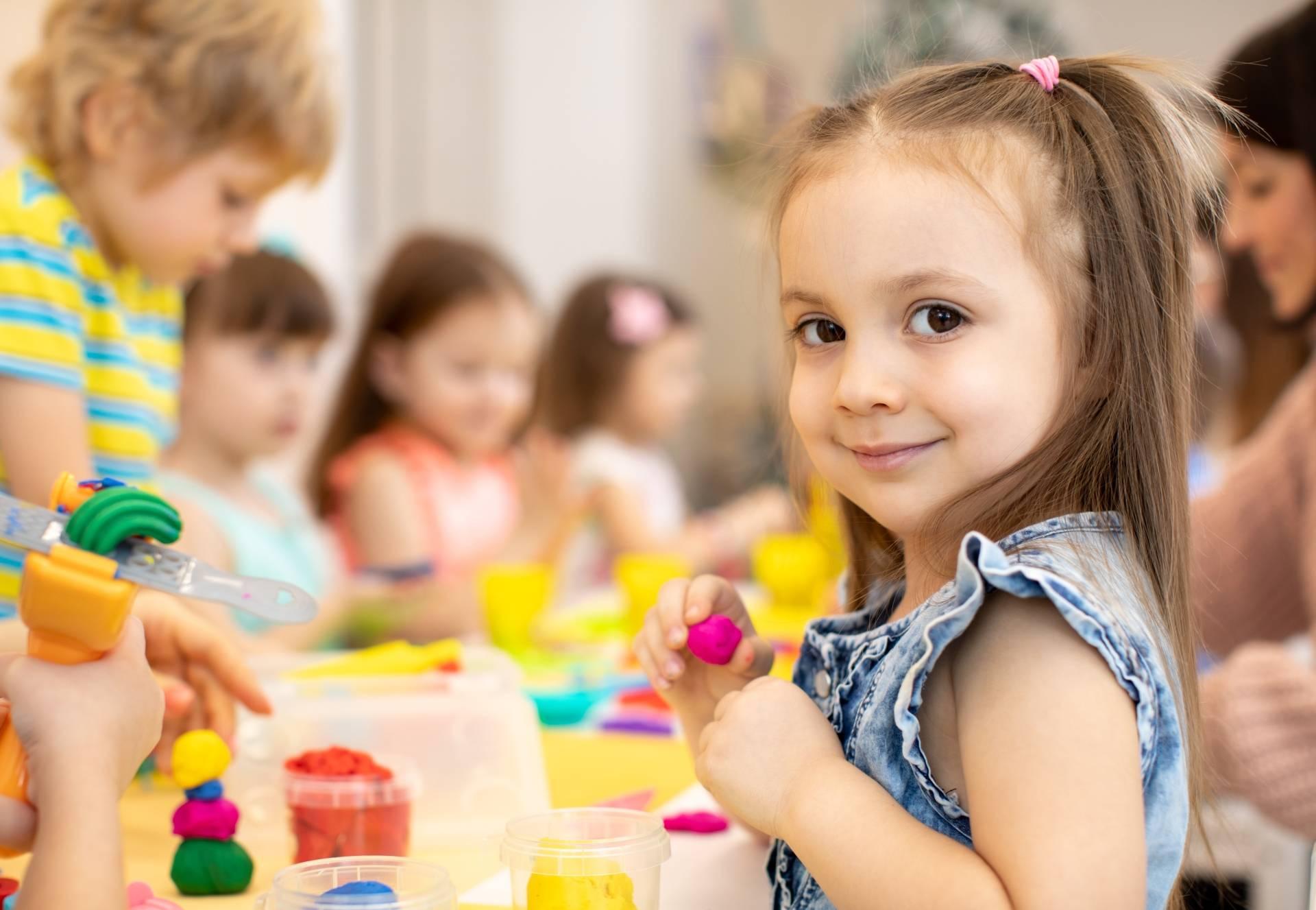 Owsiki - jak się ich pozbyć? Dziewczynka w przedszkolu siedzi przy stole z innymi dziećmi i bawi się plasteliną i farbami.