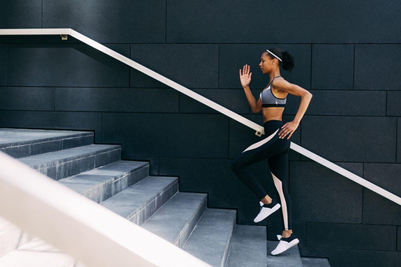 Pamięć mięśniowa - czym jest? Jak działa pamięć ciała i pamięć ruchowa? Wysportowana kobieta w sportowym stroju wbiega po schodach.