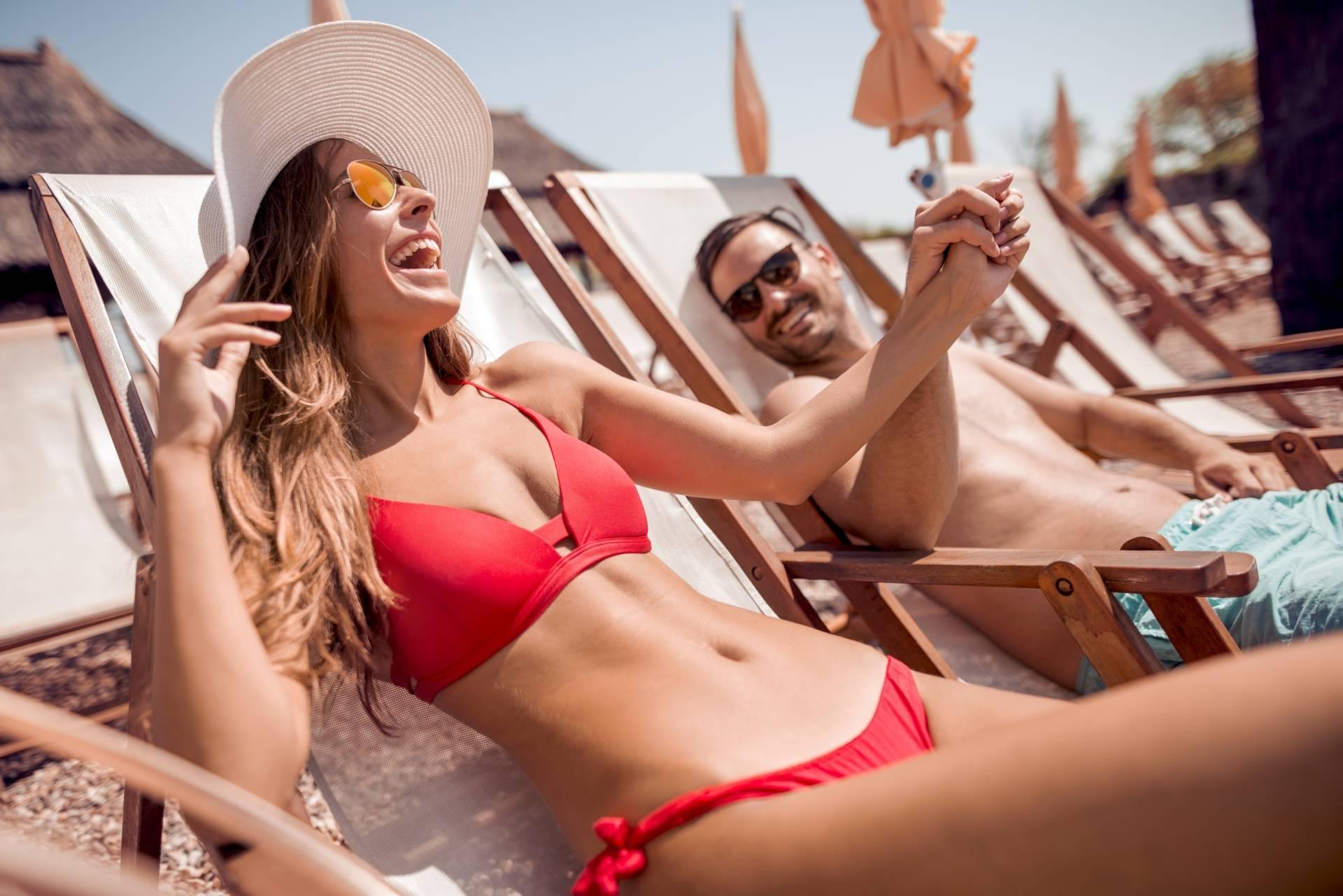 Przebarwienia na twarzy i plamki na ciele - jak ich uniknąć po wakacjach? Szczęśliwa para wypoczywa na leżakach na plaży.