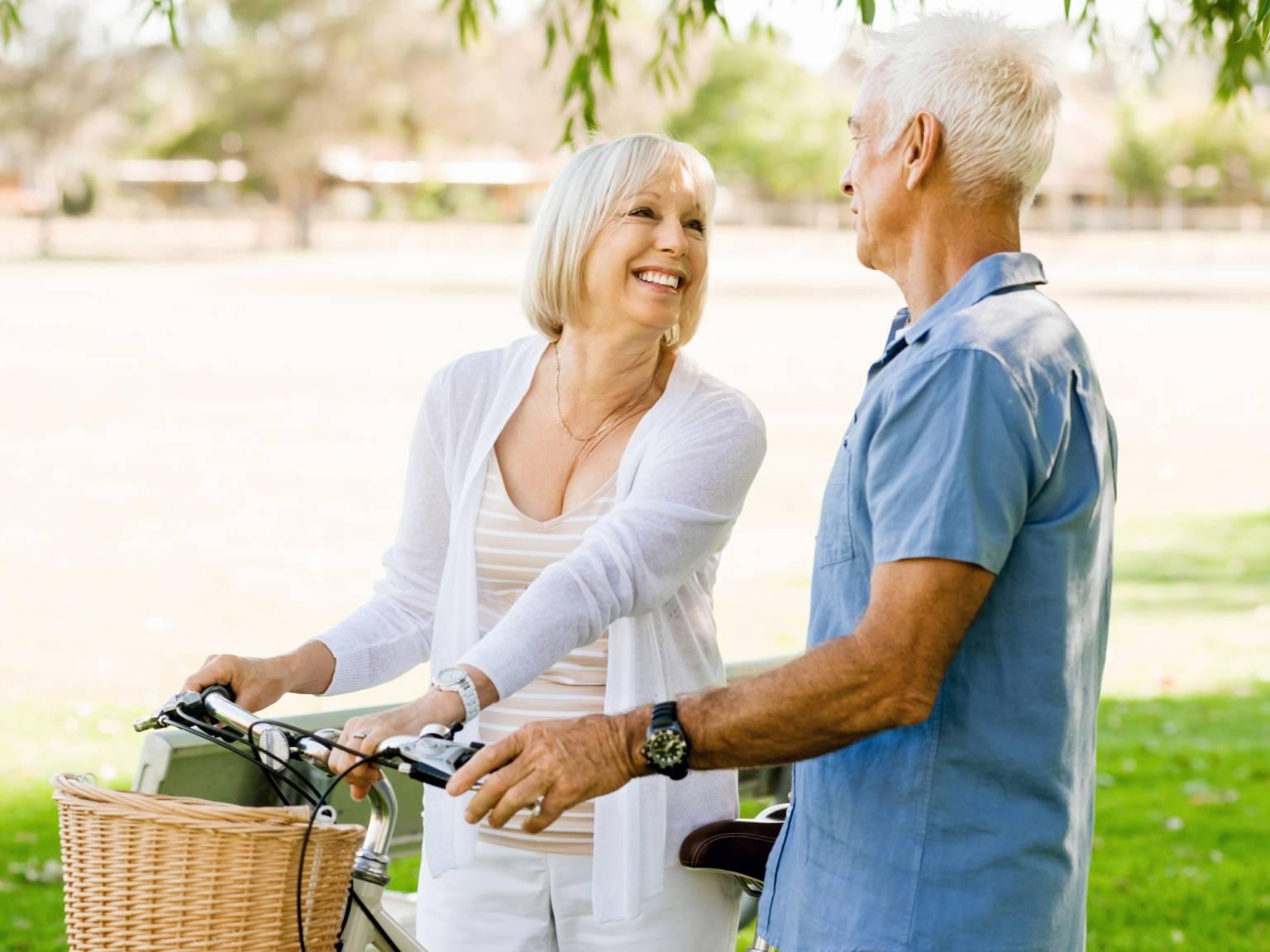 Leki roślinne i homeopatia na menopauzę - jakie preparaty łagodzą objawy klimakterium? Uśmiechnięci atrakcyjni seniorzy na przejażdżce rowerowej.