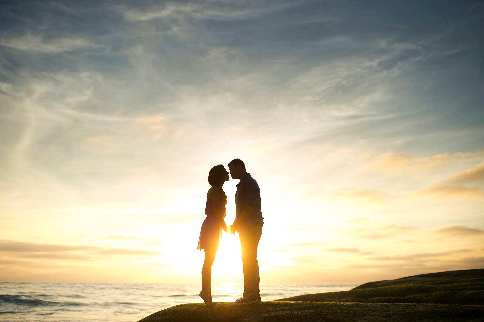 Leczenie niepłodności w medycynie chińskiej. Kobieta i mężczyzna stoją na skarpie nad oceanem o zachodzie słońca. Trzymają się za ręce i całują.