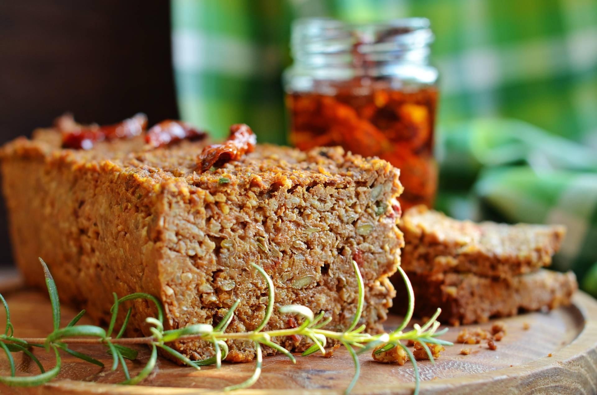 Pasztety wegetariańskie i wegańskie - z czego można je zrobić? Pasztet z soczewicy na drewnianej desce w kuchni.