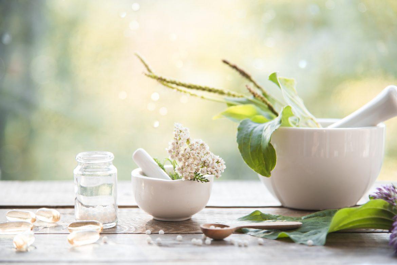 Lek homeopatyczny Phosphorus na energię i zwiększenie sił witalnych. Liście roślin w białym moździerzu stojącym na stole w ogrodzie, obok leżą granulki leków homeopatycznych.