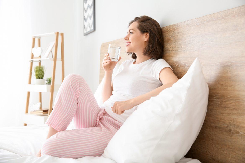 Kranówka czy woda butelkowana - jaką wybrać? Kobieta w piżamie pije szklankę wody o poranku, siedząc na łóżku w sypialni.