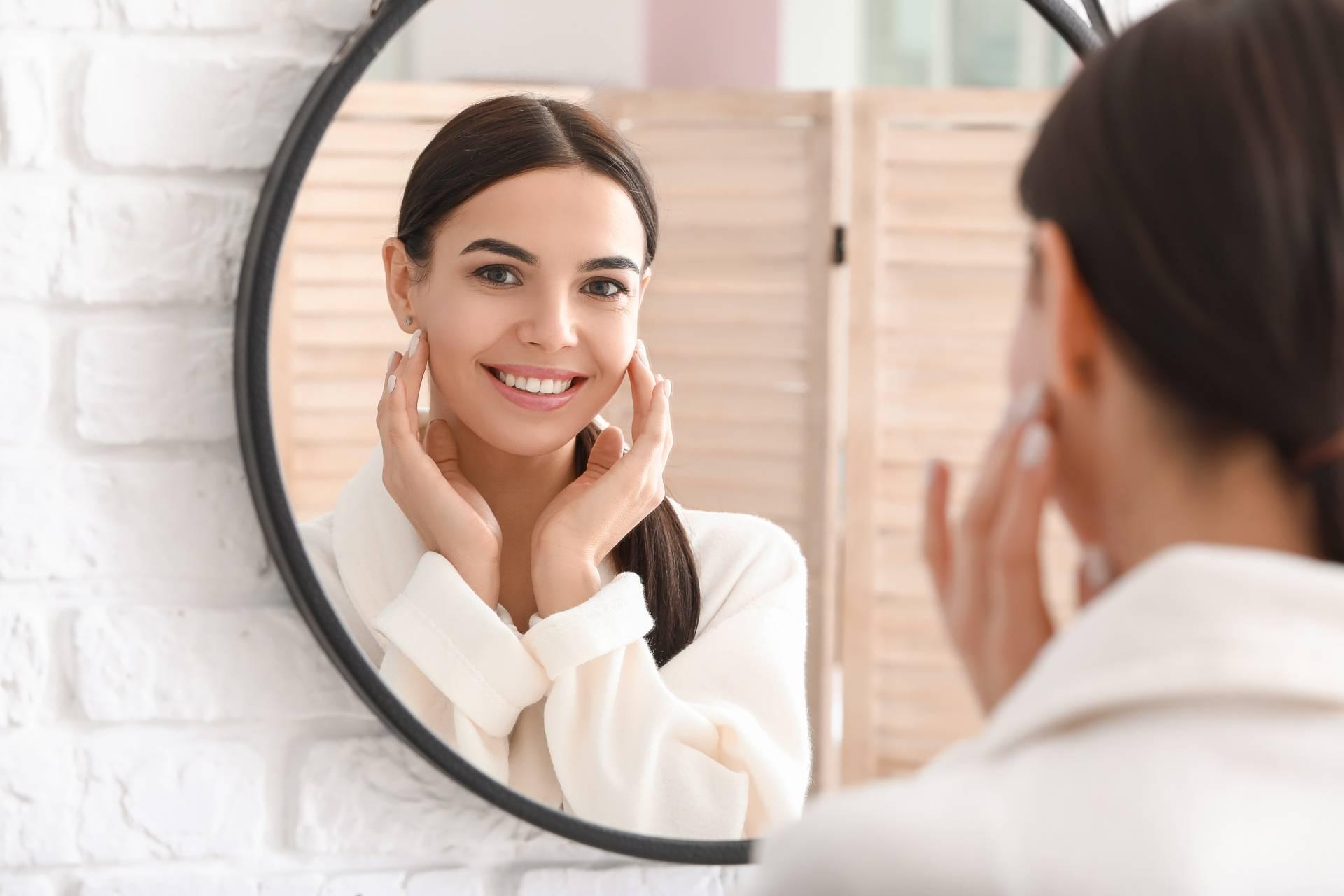 Olejek arganowy do pielęgnacji twarzy. Młoda kobieta w białym szlafroku dotyka dłońmi twarzy uśmiechając się do lustra.