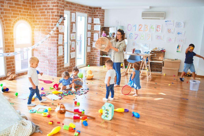 Adaptacja w przedszkolu - jak pomóc dziecku zaaklimatyzować się w nowym miejscu? Pani wychowawczyli bawi się z przedszkolakami w sali zabaw w przedszkolu.