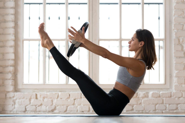 Pilates - ćwiczenia dla początkujących. Jak ćwiczyć pilates w domu? Młoda kobieta trenuje pilates z pomocą obręczy.
