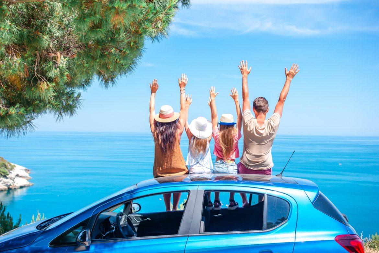 Beata Sadowska: podróże z dziećmi nie takie straszne, jakby się mogło wydawać. Dziennikarka i podróżniczka opowiada o tym, w co się bawi z dziećmi w podróży. Szczęśliwa rodzina na wakacjach siedzi na dachu samochodu z wyciągniętymi do góry rękami i podziwia widok na morze.