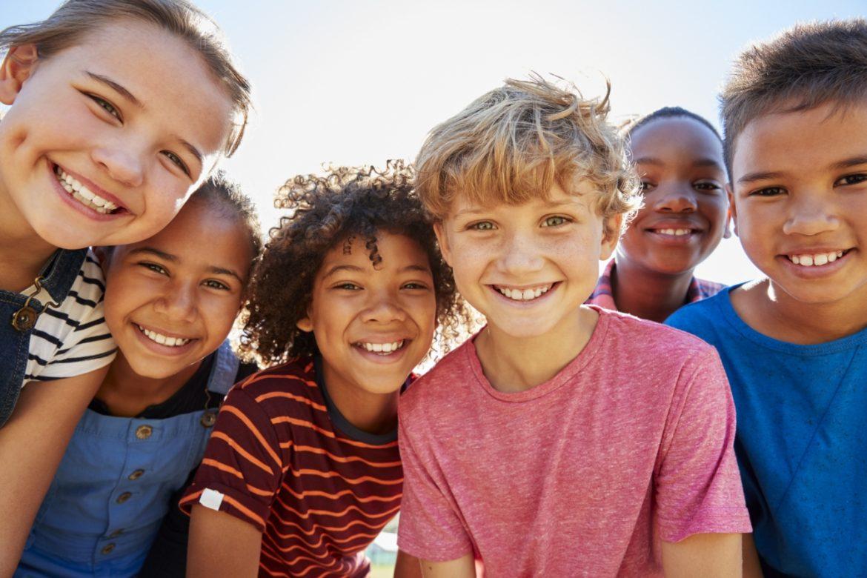 Jak nauczyć dziecko pozytywnego myślenia? Grupa uśmiechniętych dzieci o różnym pochodzeniu etnicznym patrzy w obiektyw aparatu.