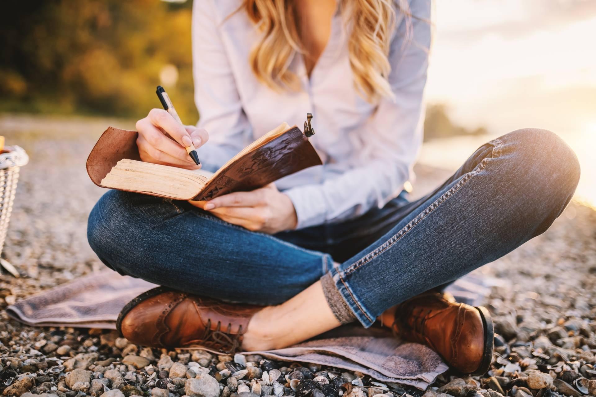 Dziennik wdzięczności w ramach medytacji wdzięczności. Młoda kobieta w koszuli z kołnierzykiem, jeansach i eleganckich mokasynach siedzi na plaży i robi notatki w dzienniku.
