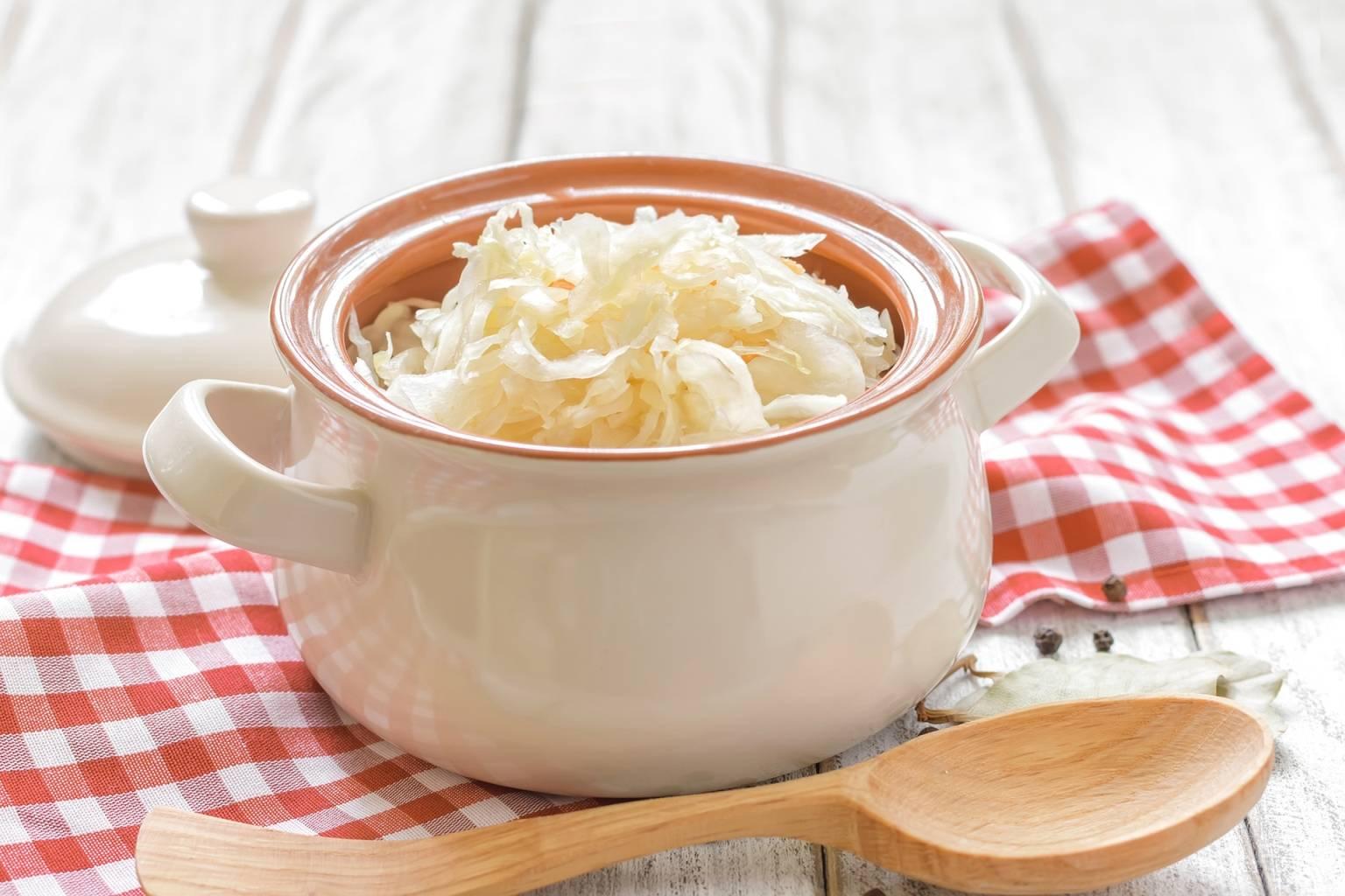 Kiszona kapusta w białej misce z pokrywką leży na ściereczce kuchennej w ciało-czerwoną kratkę. Naturalne probiotyki wzmacniają odporność.