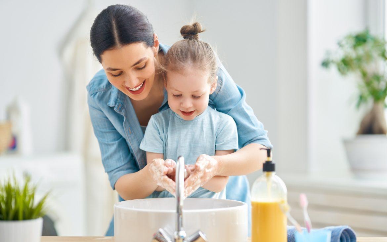 Aby zapobiec rozprzestrzenianiu się koronawirusa trzeba często myć ręce. Jak zadbać o przesuszone dłonie? Jakie są najlepsze domowe sposoby na suche dłonie? Mama uczy córkę jak myć ręce.