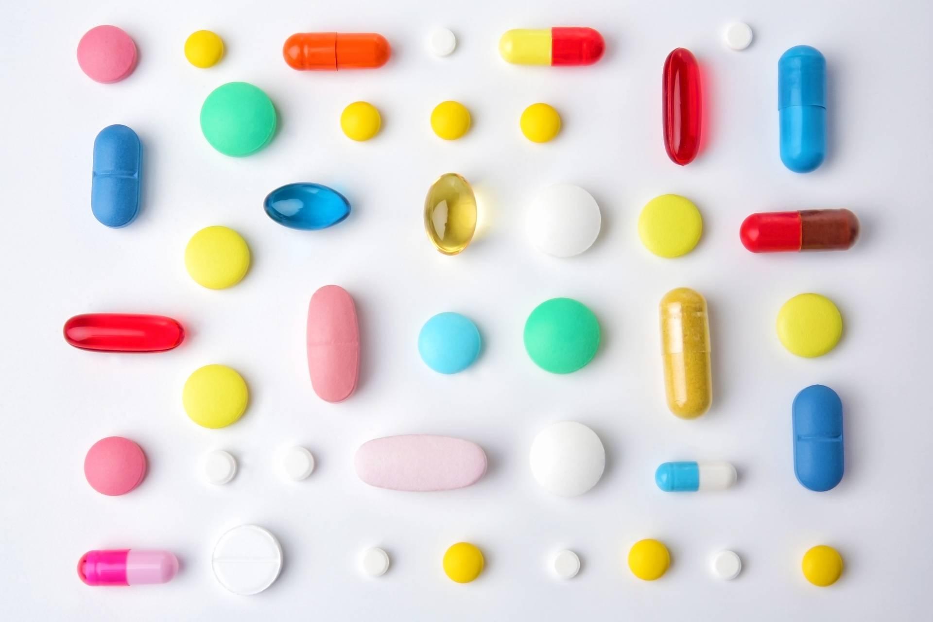 Co to są probiotyki? Które szczepy bakterii są probiotyczne? Kolorowe pigułki w różnym kształcie leżą na białym blacie.