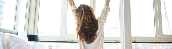 Praktyka i medytacja wdzięczności, czyli jak dobrze zacząć dzień. Młoda kobieta w białej koszuli wstaje z łóżka o poranku. siedząc jeszcze na łóżku, przeciąga się patrząc w okna.