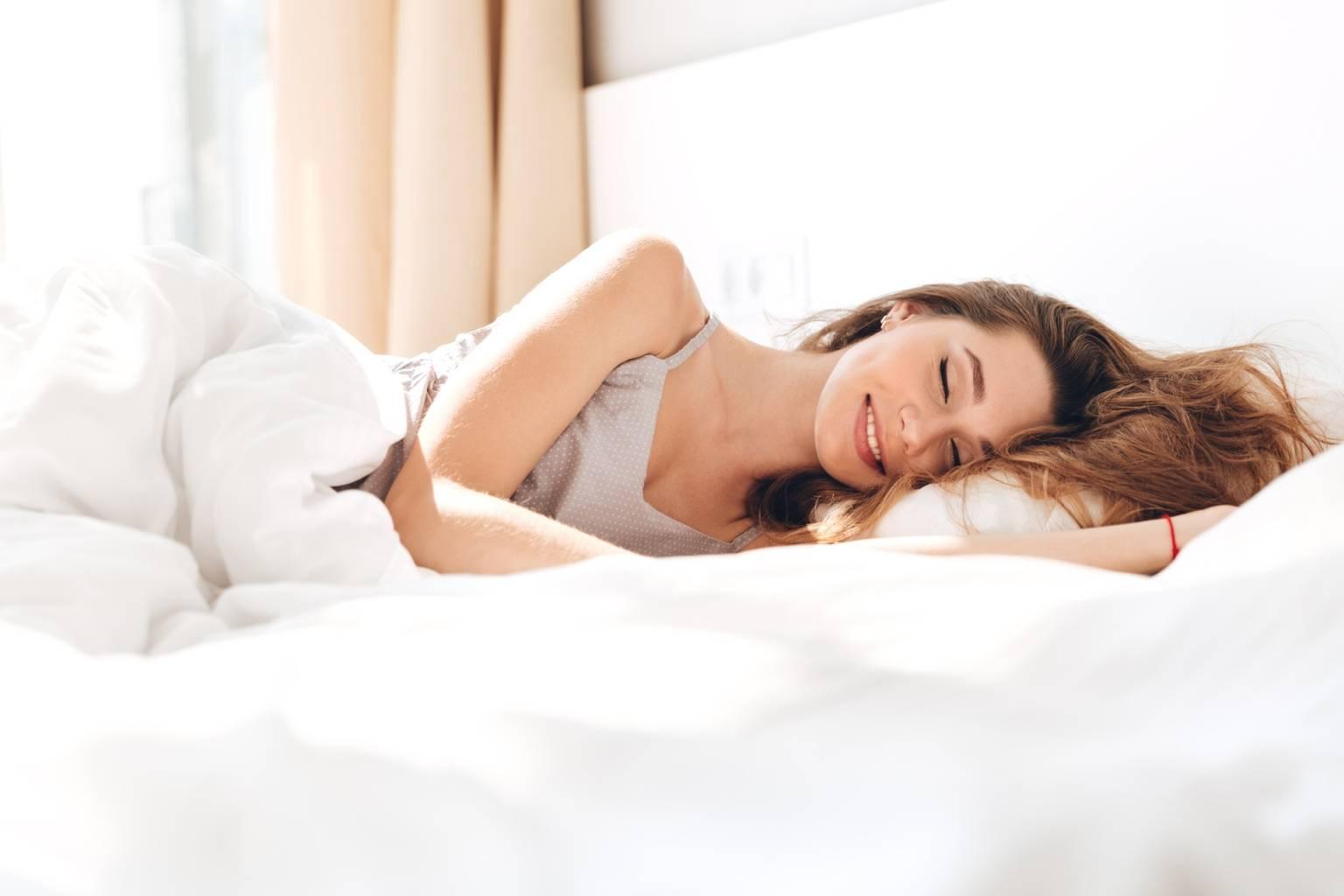 Praktyka i medytacja wdzięczności o poranku. Młoda atrakcyjna zaspana dziewczyna leży w łóżku o poranku i uśmiecha się do siebie.