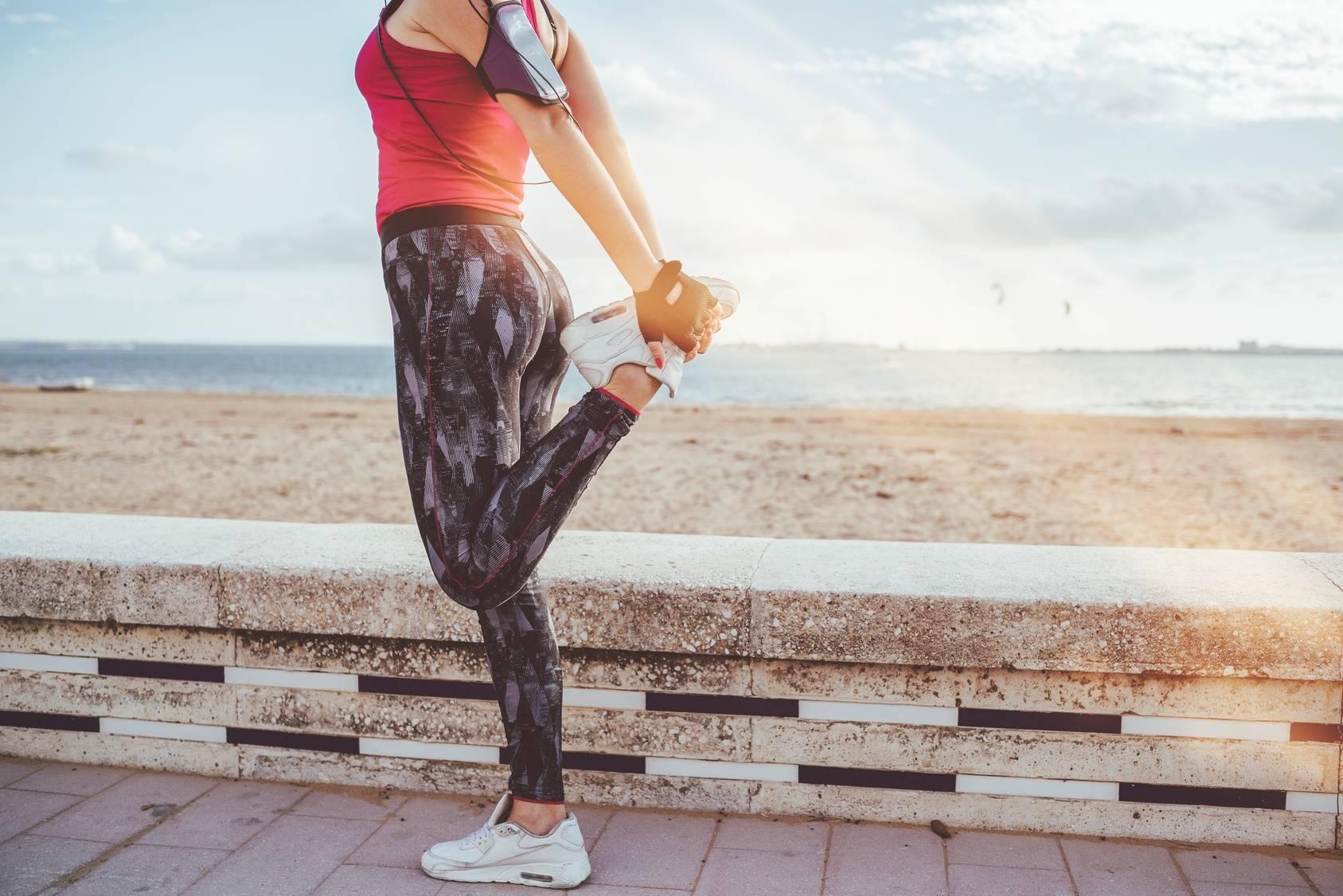 Jak powinna wyglądać rozgrzewka przed treningiem? Kobieta w sportowym stroju przygotowuje się do biegania na świeżym powietrzu.