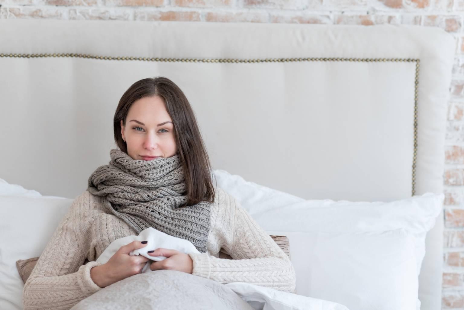 Sposoby na katar i kichanie. Przeziębiona kobieta leży w łóżku pod kołdrą, opatulona szalikiem, patrze prosto w aparat i delikatnie się uśmiecha.