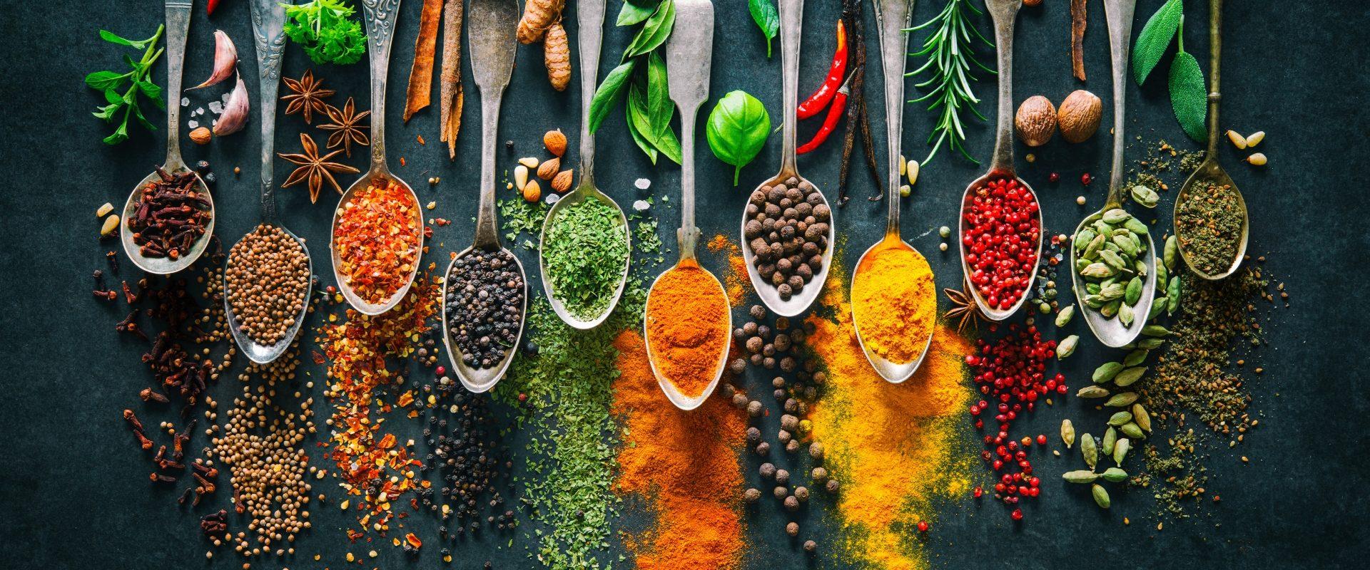 Jak gotować jesienią według medycyny chińskiej? Rozgrzewające przyprawy i zioła na ułożonych obok siebie łyżeczkach i czarnym tle.