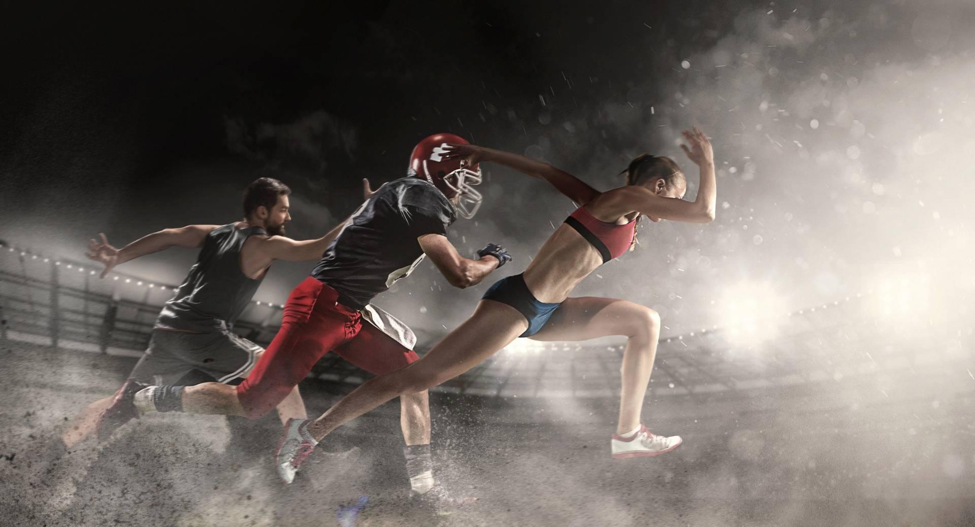 Psychologia sportu: jak odnieść sukces? Zawodnicy z różnych dyscyplin sportowych biegną po stadionie w świetle reflektorów.