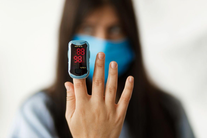 Pulsoksymetr - czym jest i jak działa? Kobieta w maseczce pokazuje pulsoksymetr założony na palec wskazujący.