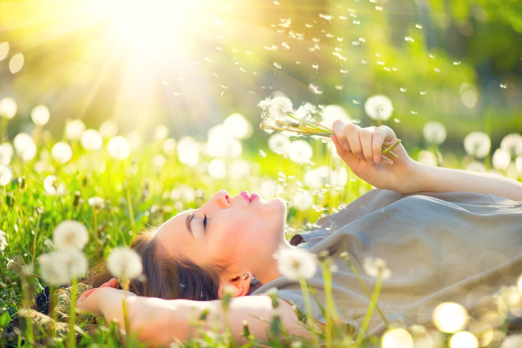 Alergia w medycynie chińskiej. Młoda atrakcyjna kobieta leży na plecach na łące wśród dmuchawów i zdmuchuje pyłki z dmuchawca, którego trzyma w ręku.